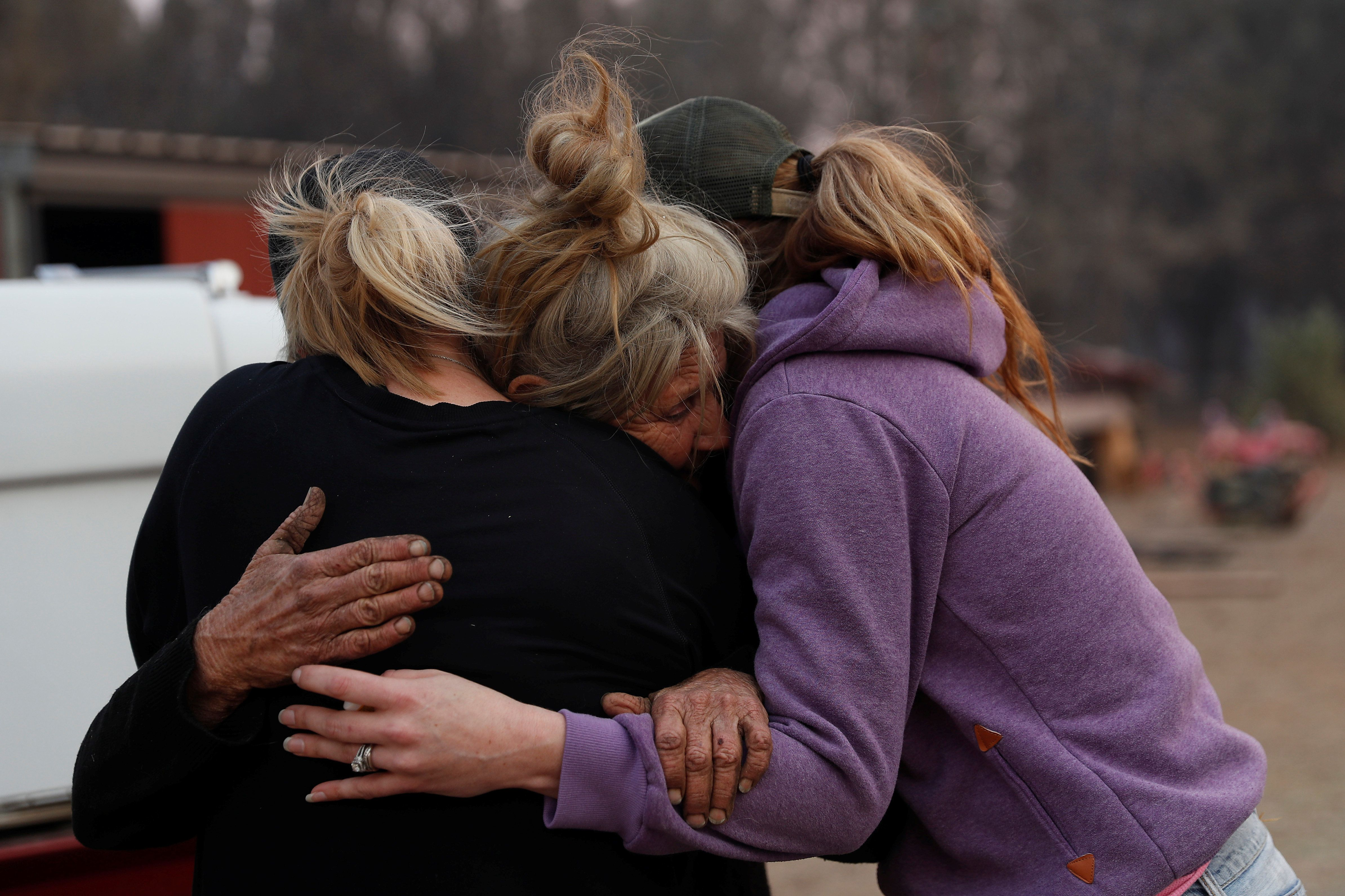 Cathy Fallon (C) who stayed behind to tend to her horses during the Camp Fire, embraces Shawna De Long (L) and April Smith who brought supplies for the horses in Paradise, California, U.S. November 11, 2018. REUTERS/Stephen Lam