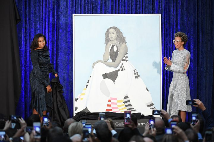 Former first lady Michelle Obama and artist Amy Sherald stand next to Obama's portrait as paintings of she and former Preside