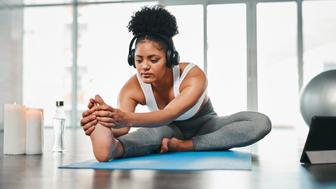 Shot of a young woman listening to music while doing yoga