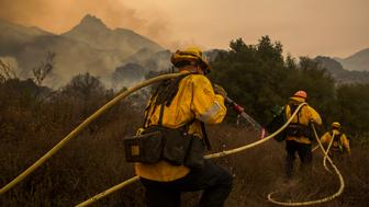 MALIBU, CA - NOVEMBER 10: Los Angeles County firefighters attack flames approaching the Salvation Army camps in Malibu Creek State Park during the Woolsey Fire on November 10, 2018 near Malibu, California. The Woolsey fire has burned over 70,000 acres and has reached the Pacific Coast at Malibu as it continues grow.   (Photo by David McNew/Getty Images)