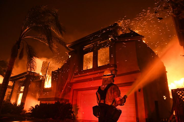 A firefighter battles a house fire as the Woolsey Fire burns in Oak Park, a community in Southern California, early Friday mo