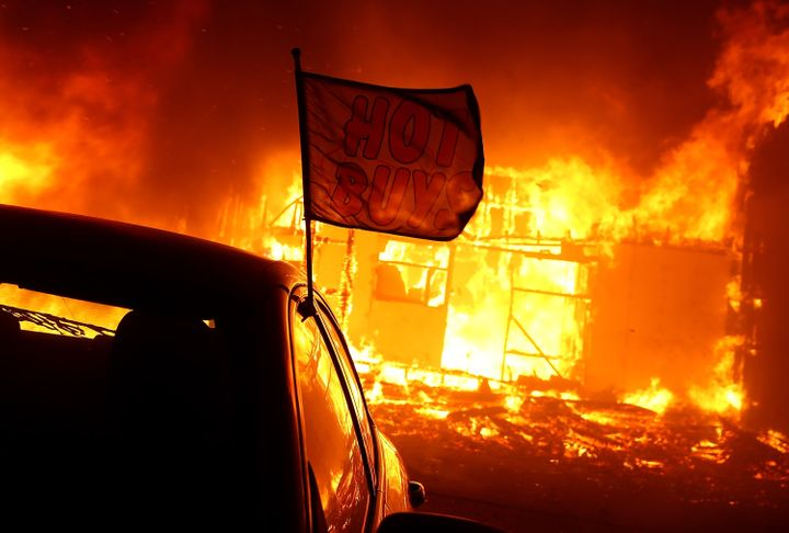 The Camp fire moves through a car dealership on Nov. 8, 2018, in Paradise, California. Fueled by high winds and low humidity,