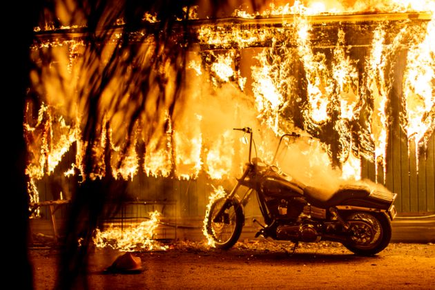 A structure and a motorcycle burn at an RV park during the Woolsey fire in Malibu, California, Nov. 10,
