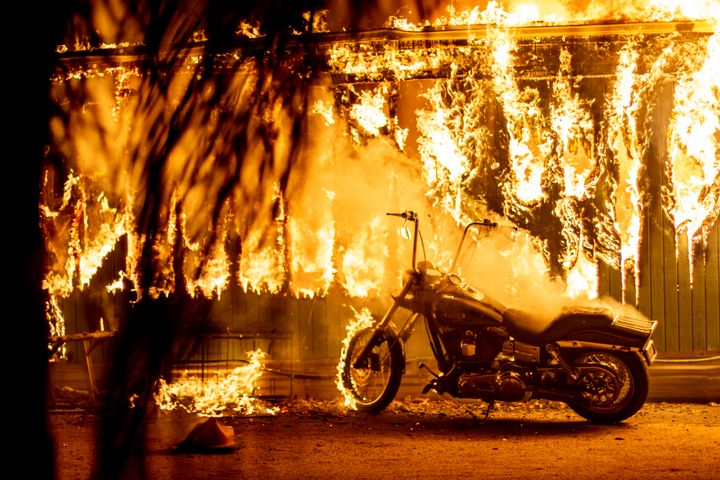 A structure and a motorcycle burn at an RV park during the Woolsey fire in Malibu, California, Nov. 10, 2018.