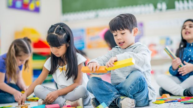 A group of kindergarten kids are indoors in their school. They are sitting on the carpet and playing with toy blocks.