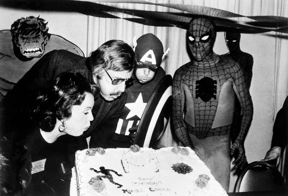 Mighty Marvel comic-book publisher Stan Lee, center left, blows out the candles on the Marvel Comics birthday cake at opening