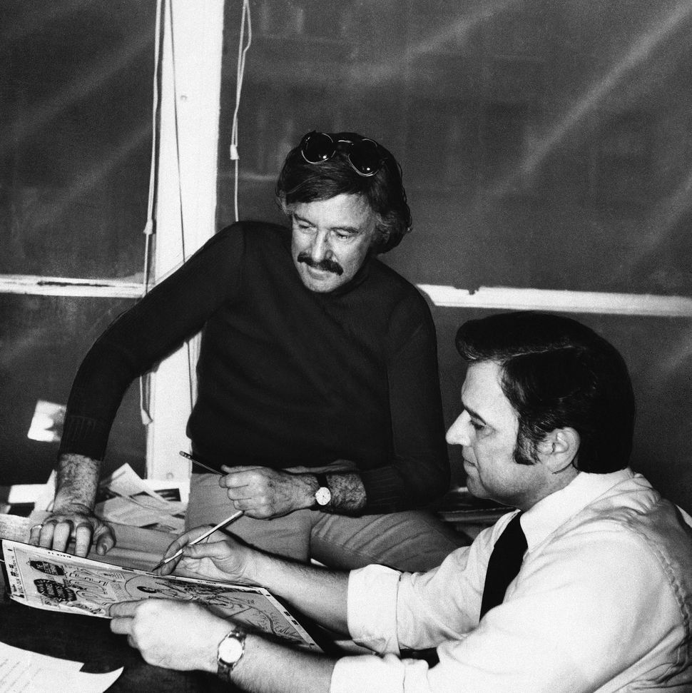 Stan Lee, in dark sweater, publisher and editor of Marvel Comics, and his art director, John Romita, look at a drawing on Mar