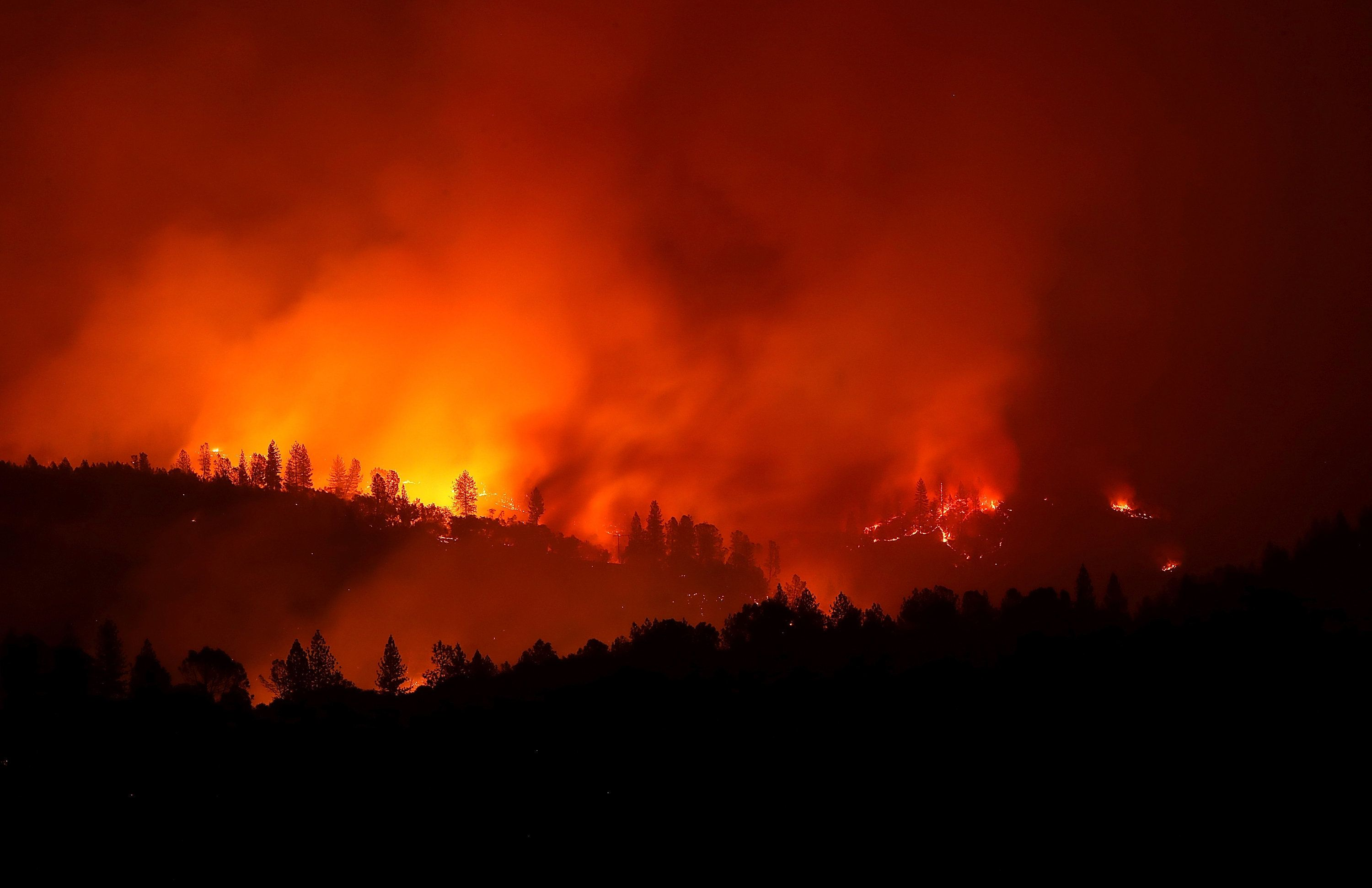 OROVILLE, CA - NOVEMBER 11:  The Camp Fire burns in the hills on November 11, 2018 near Oroville, California. Fueled by high winds and low humidity the Camp Fire ripped through the town of Paradise charring over 105,000 acres, killed 23 people and has destroyed over 6,700 homes and businesses. The fire is currently at 25 percent containment.  (Photo by Justin Sullivan/Getty Images)