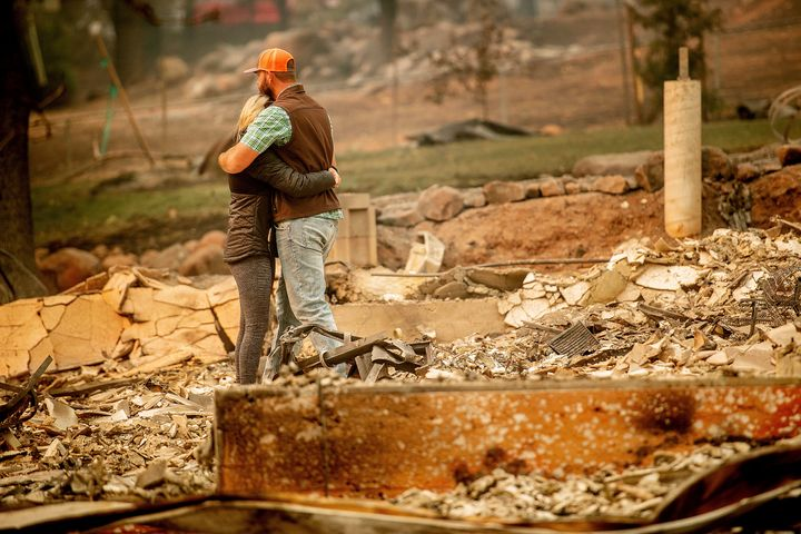 Chris and Nancy Brown embrace while searching through the remains of their home, leveled by the Camp fire, in Paradise, Calif