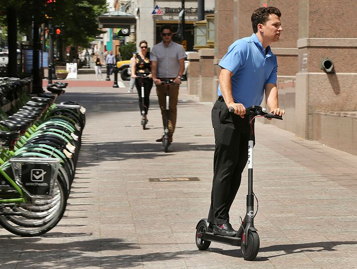 Mark Rodgers rides an electric scooter in Salt Lake City this summer. Cities and states are trying to figure out how to regul