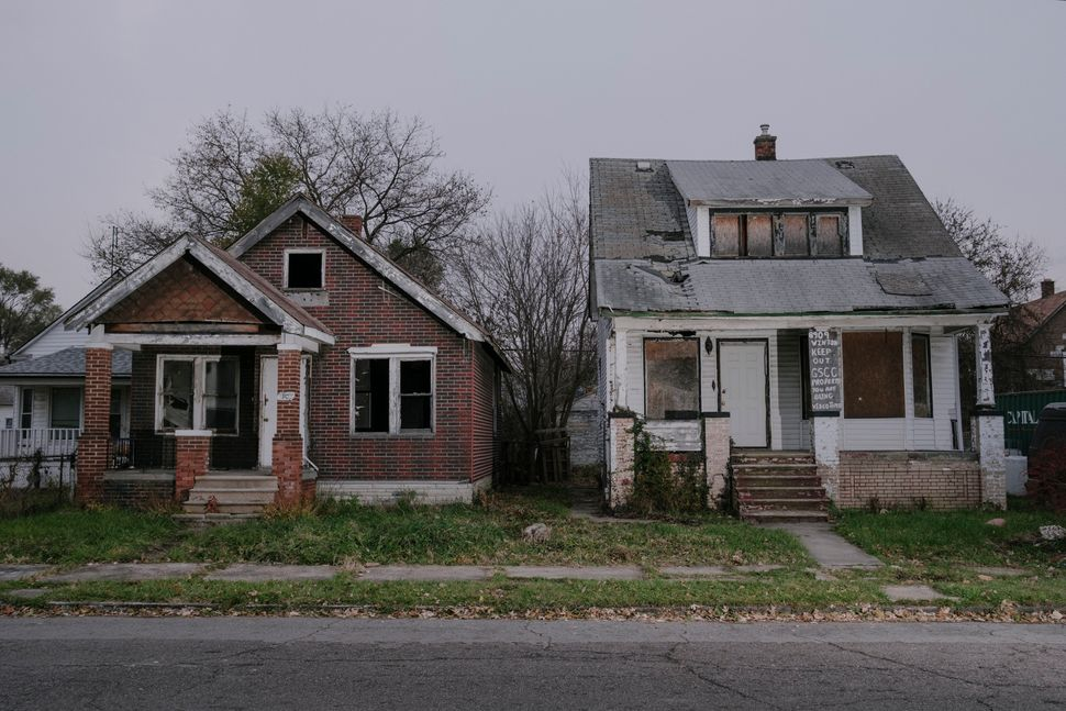 At left, a house owned by the Detroit Land Bank Authority and, at right, a vacant house owned by Covington...