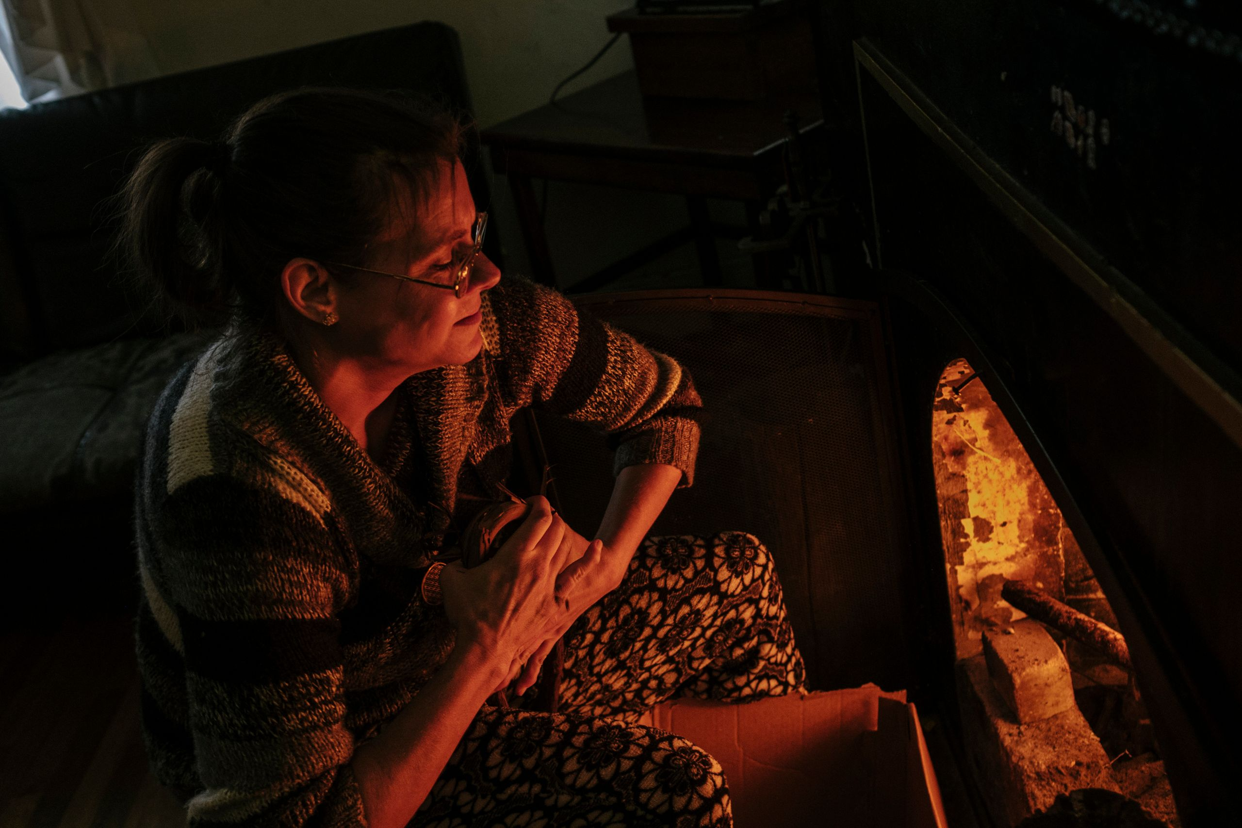 Fritz builds a fire using wood collected from the alley to heat her house.
