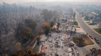 File - In this Aug. 10, 2018 file photo, homes destroyed by a wildfire are seen from an aerial view in the Mary Lake Subdivision in Redding, Calif. Fire crews have made great gains against a wildfire that has been burning for more than a month in Northern California, where it destroyed nearly 1,100 homes and killed eight people. The California Department of Fire and Forestry Protection says the blaze burning in and around the city of Redding is 93 percent contained as of Wednesday, Aug. 22, 2018. (AP Photo/Michael Burke, File)