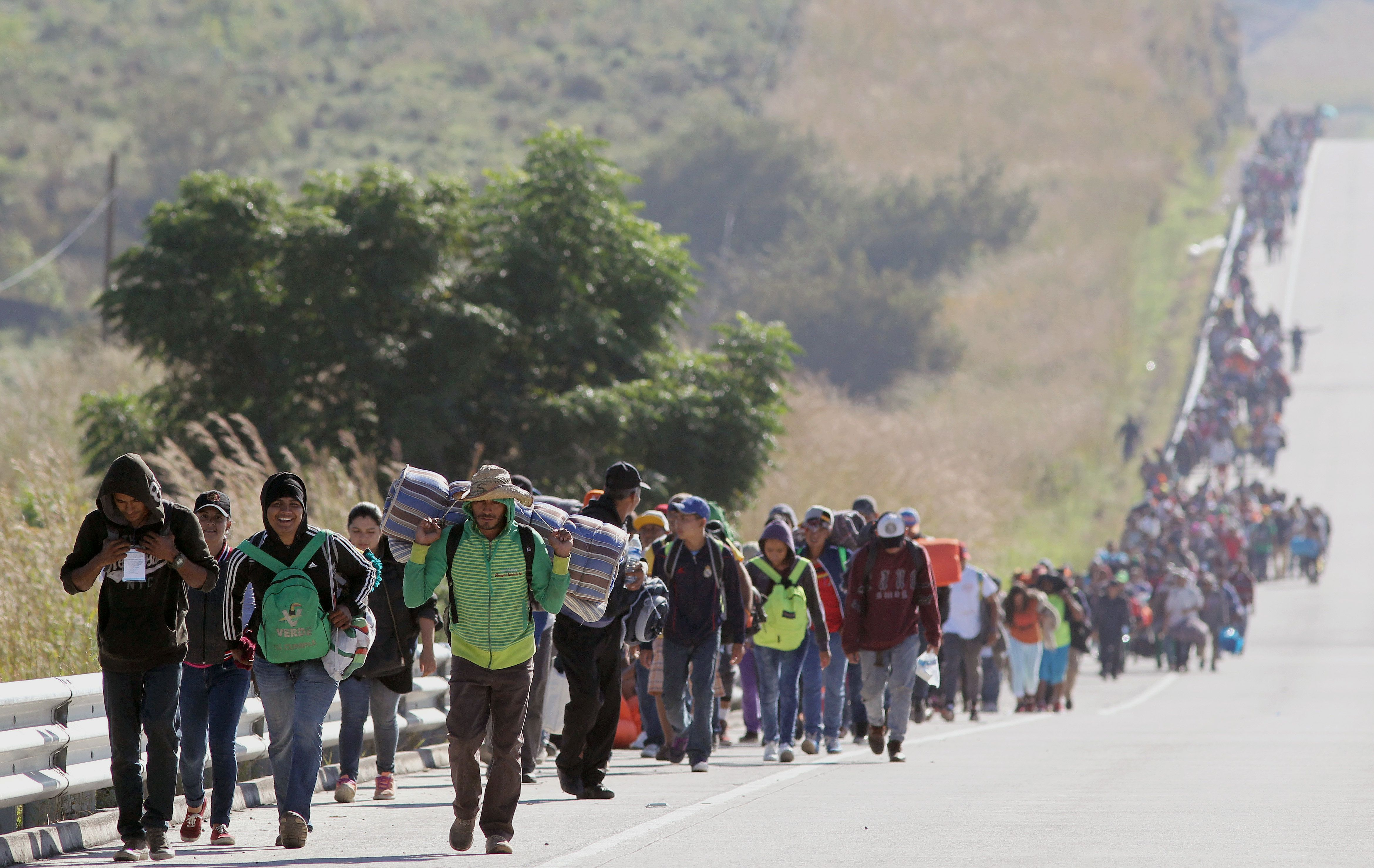 Migrants from poor Central American countries -mostly Hondurans- moving towards the United States in hopes of a better life, walk along the road between Zapopan and Tequila in the Mexican state of Jalisco, on their trek north, on November 13, 2018. - Defense Secretary Jim Mattis said Tuesday he will visit the US-Mexico border, where thousands of active-duty soldiers have been deployed to help border police prepare for the arrival of a 'caravan' of migrants. (Photo by ULISES RUIZ / AFP)        (Photo credit should read ULISES RUIZ/AFP/Getty Images)