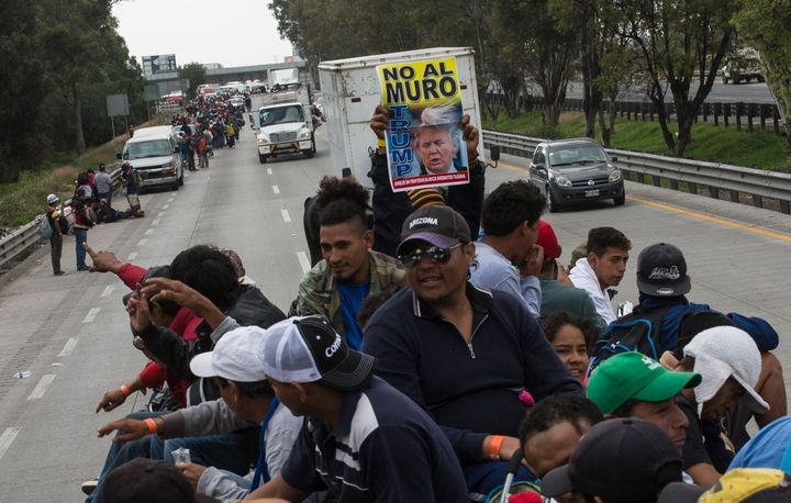 """A Central American migrant holds a sign with a message that reads in Spanish: """"No to the wall Trump"""", while hitching a ride o"""