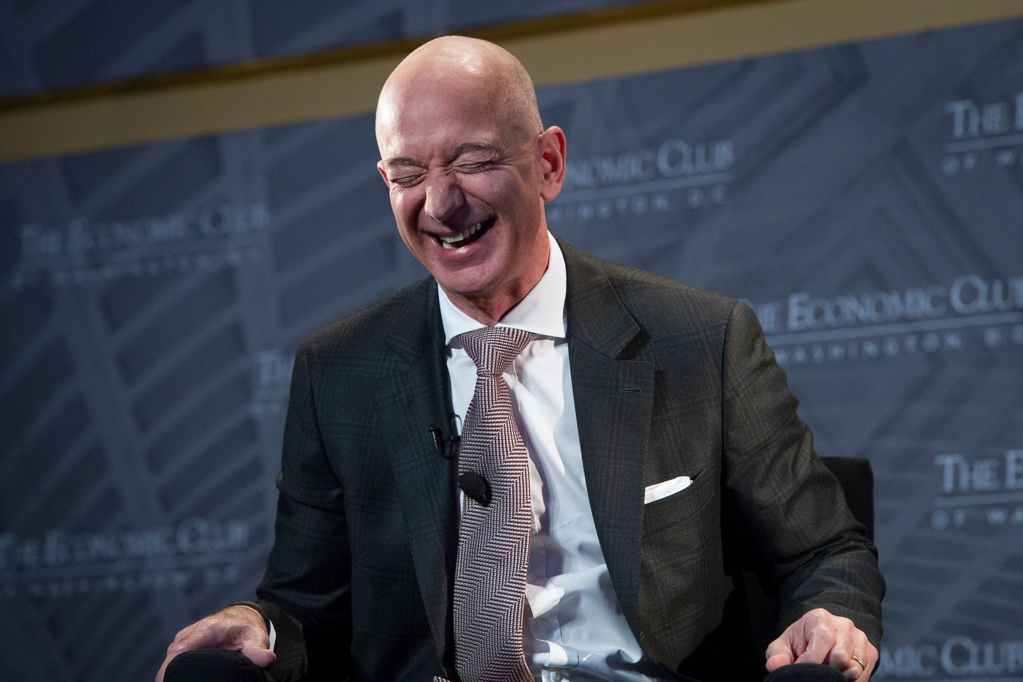 Jeff Bezos, Amazon founder and CEO, laughs as he speaks at The Economic Club of Washington's Milestone Celebration in Washington, Thursday, Sept. 13, 2018. Bezos said that he is giving $2 billion to start the Bezos Day One Fund which will open preschools in low-income neighborhoods and give money to nonprofits that helps homeless families. (AP Photo/Cliff Owen)