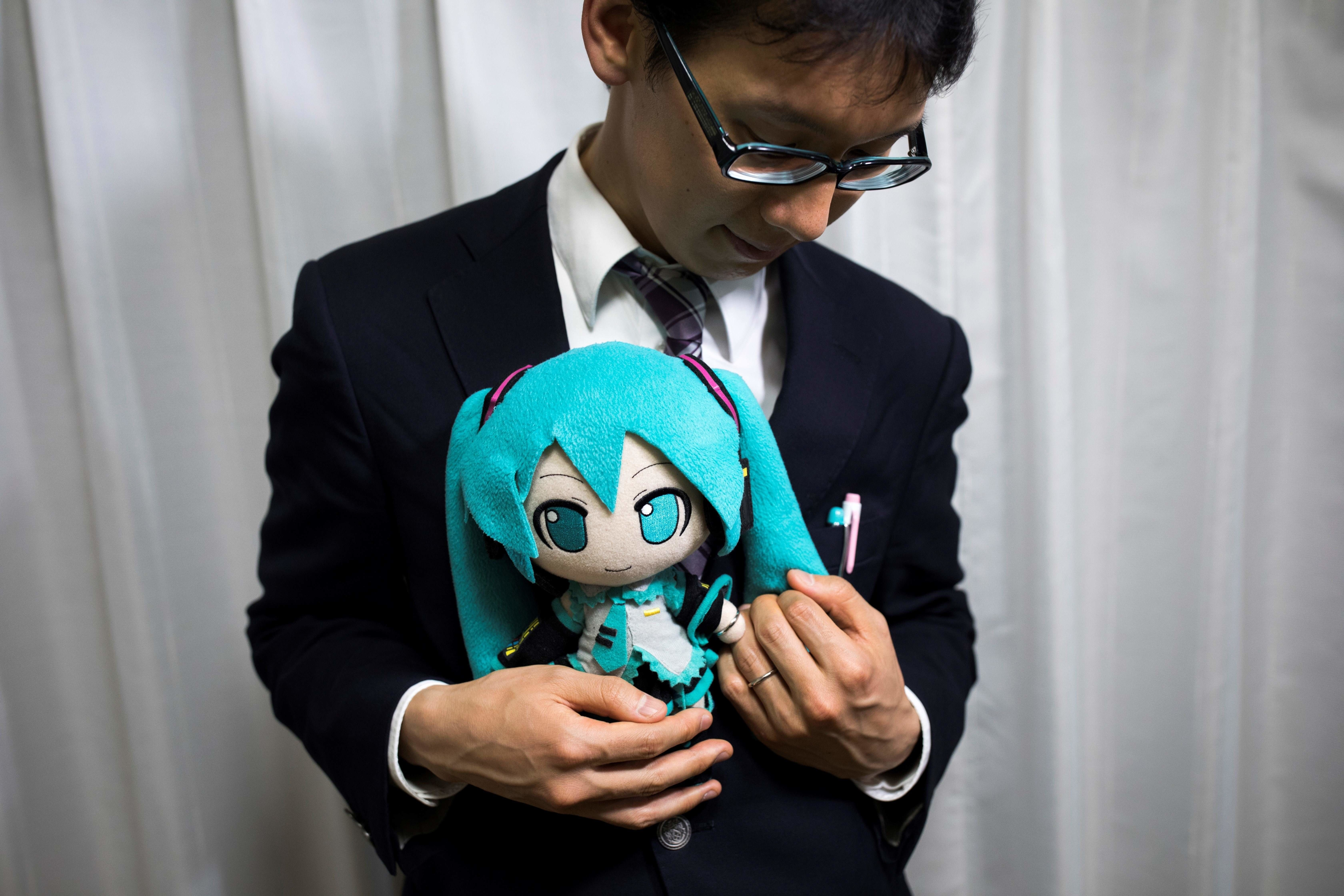In this photograph taken on November 10, 2018 Japanese Akihiko Kondo poses with a doll of Japanese virtual reality singer Hatsune Miku, as both wear their wedding rings, at his apartment in Tokyo, a week after marrying her. - Akihiko Kondo, who is an administrator at a school, married to a Japanese virtual reality singer called Hatsune Miku in early November 2018. The bride is a computer animation with saucer eyes and lengthy aquamarine pigtails who performs to adoring fans as virtual reality character . (Photo by Behrouz MEHRI / AFP) / TO GO WITH AFP STORY: Japan-culture-entertainment-computers-music-social, FOCUS by Miwa SUZUKI        (Photo credit should read BEHROUZ MEHRI/AFP/Getty Images)
