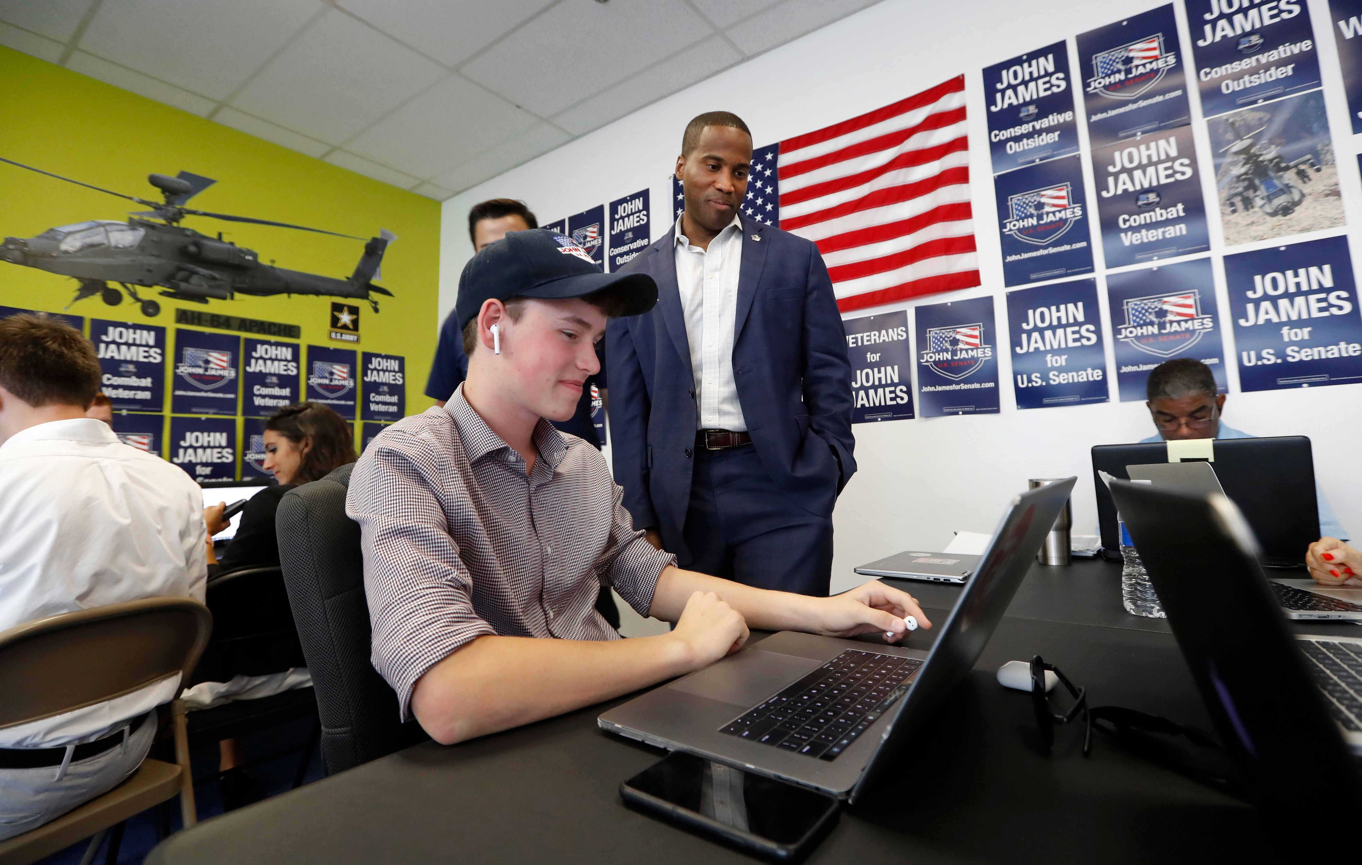 Republican U.S. Senate candidate John James talks with workers at his campaign headquarters in Livonia, Mich., Monday, Aug. 6, 2018. (AP Photo/Paul Sancya)