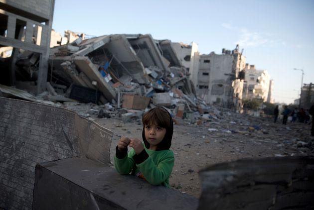 Un garçon palestinien se tient à côté des décombres du bâtiment...