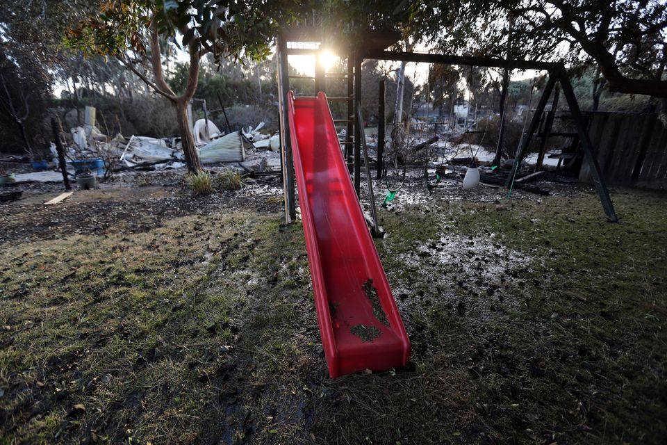 A child's slide and swingset stand behind a home destroyed by the Woolsey fire on Dume Drive in the Point...