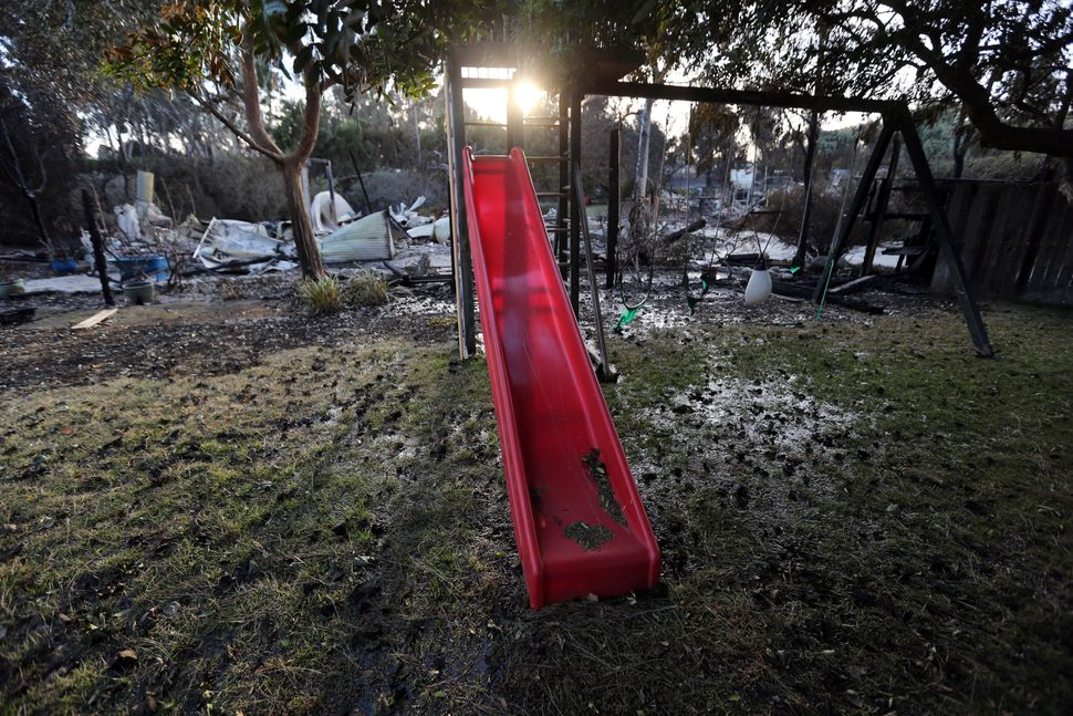 A child's slide and swingset stand behind a home destroyed by the Woolsey fire on Dume Drive in the Point Dume area of Malibu