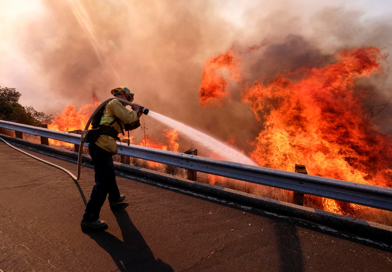 A firefighter battles a fire along the Ronald Reagan Freeway, aka state Highway 118, in Simi Valley, California, Nov. 12, 2018.