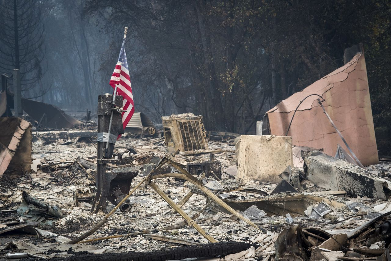 An American flag stands among burned rubble in Paradise, California, on Nov. 13. The Camp fire north of Sacramento has killed at least 42 people, injured three firefighters and destroyed 6,500 homes.