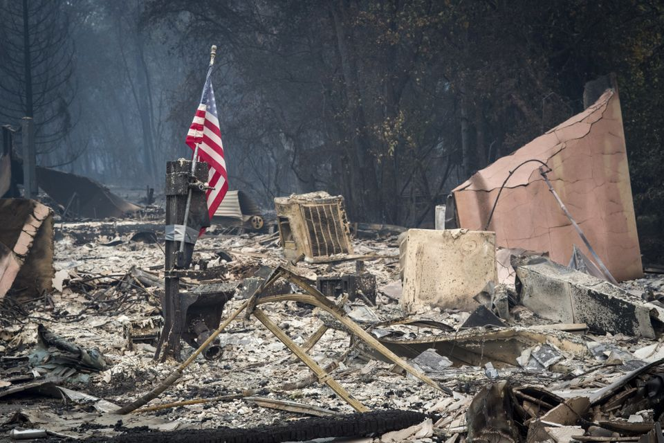 An American flag stands among burned rubble in Paradise, California, on Nov. 13. The Camp fire north...