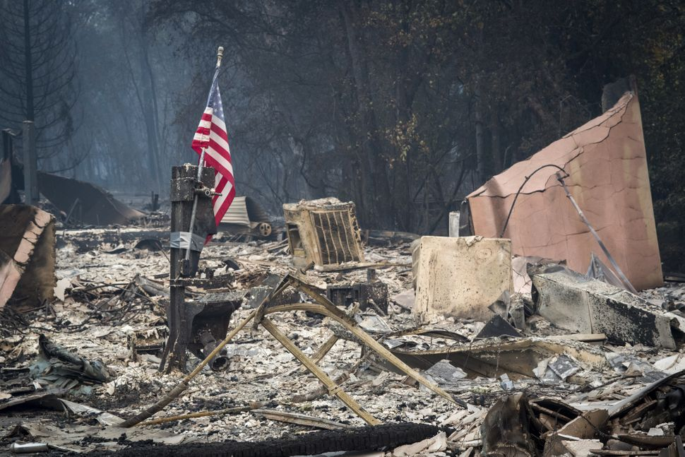 An American flag stands among burned rubble in Paradise, California, on Nov. 13. The Camp fire north of Sacramento has killed