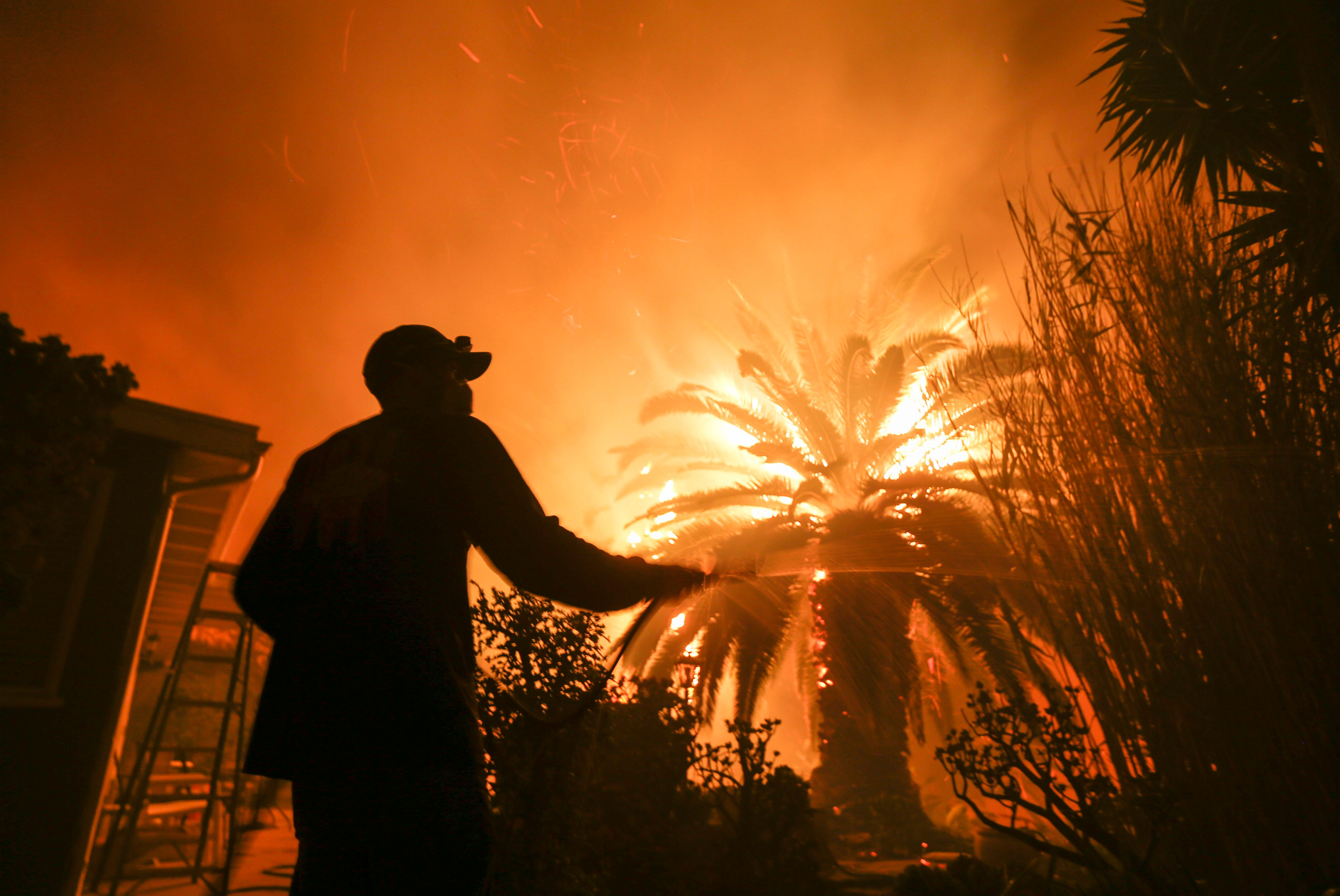 Park Billow, 27, sprays water on the hot spots in his backyard as the Woolsey fire burns in Malibu, California, Nov. 9, 2018.