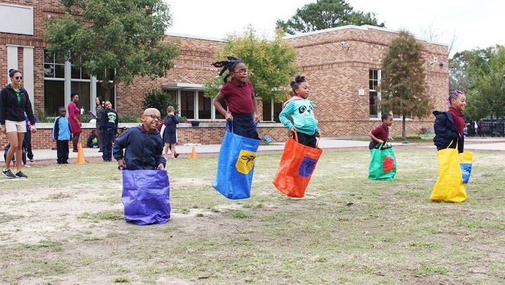 Kids at the Dufrocq School in Baton Rouge, Louisiana, compete in a sack race using equipment provided by the local parks and