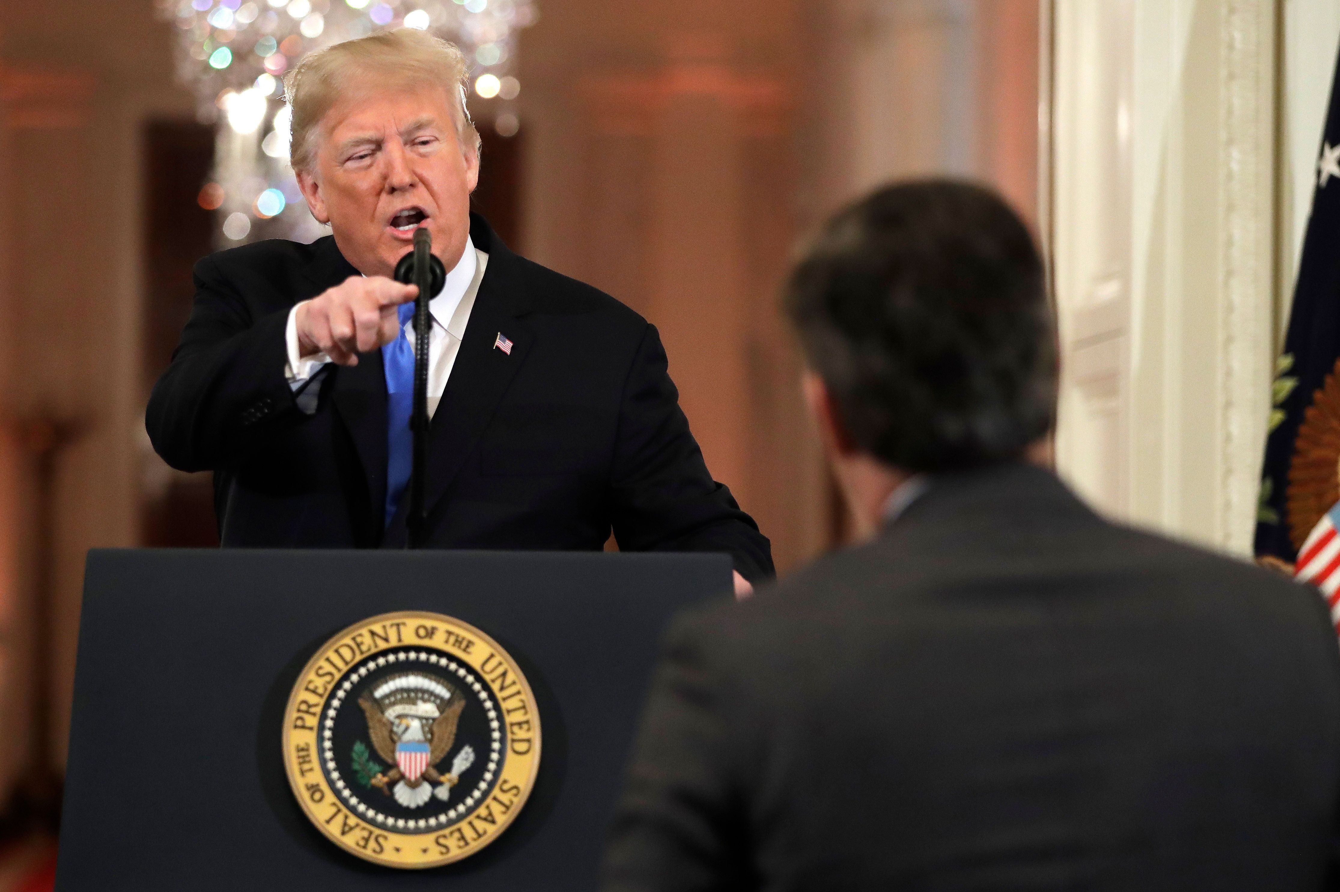 President Donald Trump points to CNN's Jim Acosta as he speaks during a news conference in the East Room of the White House l