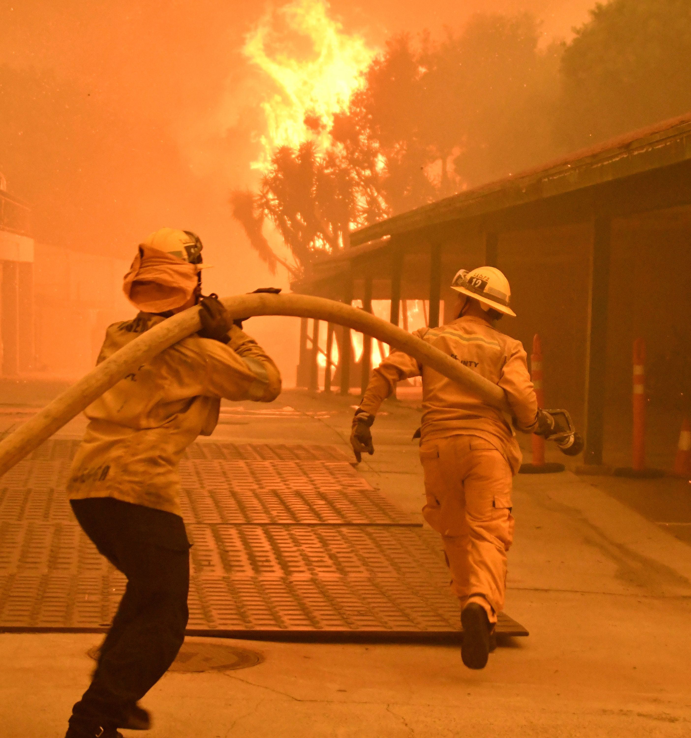 A condo unit goes up in fire from flying embers due to the Woolsey Fire, as firefighters prepare to hose down the flames, in Malibu, California, U.S. November 9, 2018. REUTERS/Gene Blevins - RC11DBC699C0