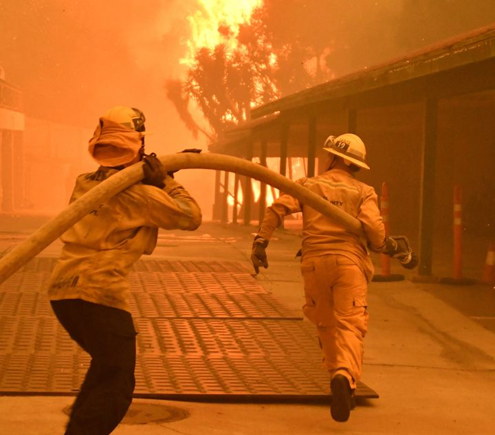 Firefighters prepare to hose down flames as the Woolsey fire consumes a condo unit in Malibu, California, on Nov. 9, 2018.