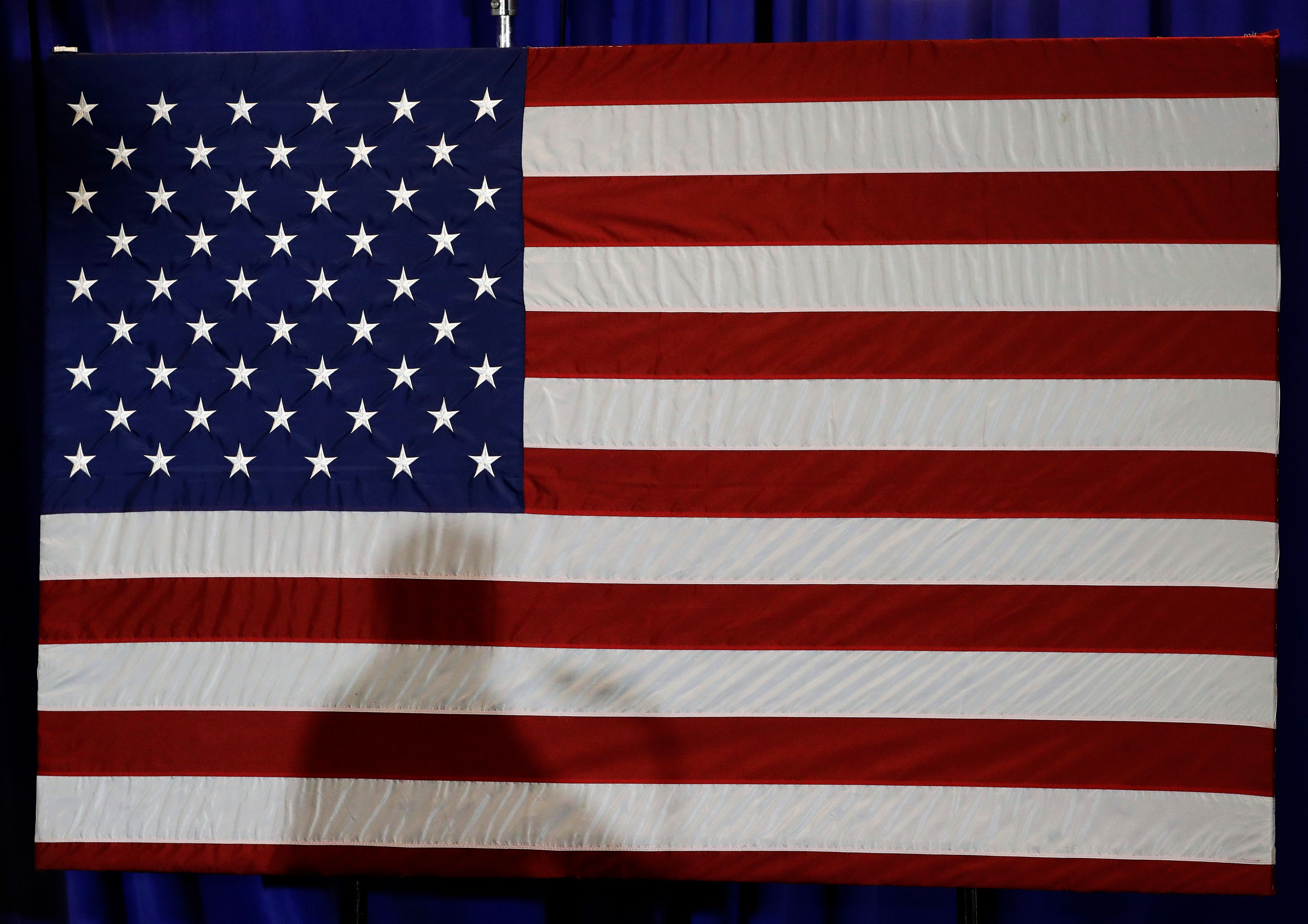 President Donald Trump's shadow is shown on an American flag as he speaks before signing an executive order at the CPCC Harris Conference Center in Charlotte, N.C., Friday, Aug. 31, 2018. (AP Photo/Chuck Burton)