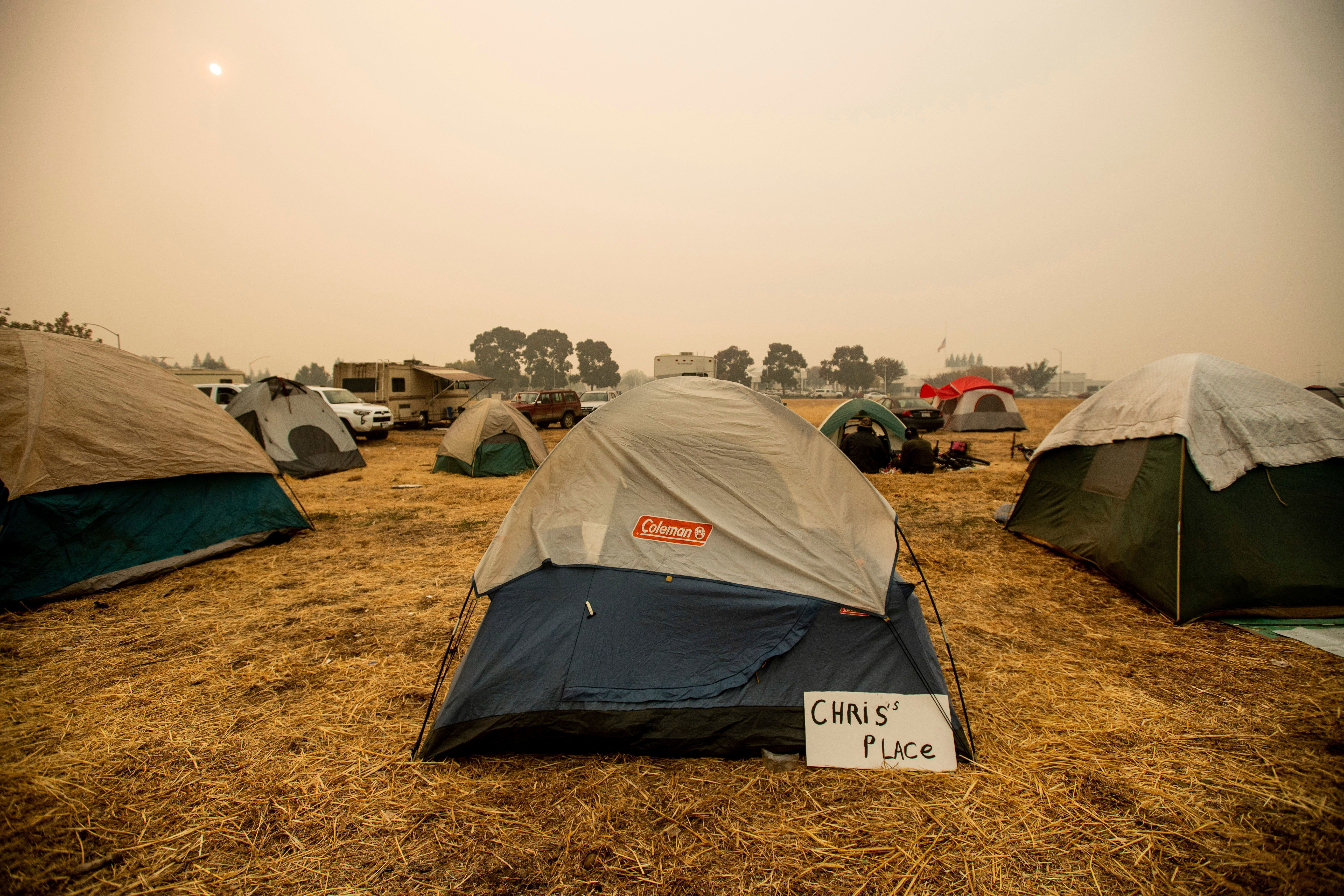 A sign hangs beside a tent at a makeshift shelter for evacuees of the Camp Fire in Chico, Calif., on Wednesday, Nov. 14, 2018. (AP Photo/Noah Berger)