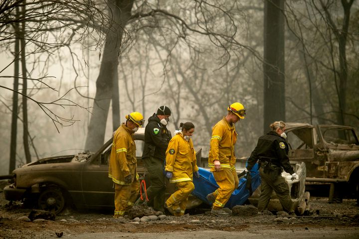 Firefighters recover the body of a Camp fire victim at the Holly Hills Mobile Estates on Wednesday in Paradise, California. T