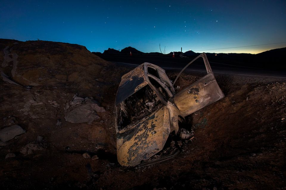 A burned car is seen crashed off the side of Mulholland Highway at night in the Santa Monica Mountains...