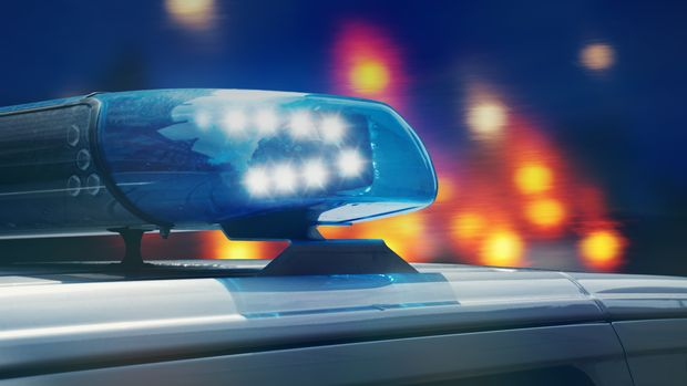 police patrol car on the road at night with flashing blue lights and backlights from other vehicles