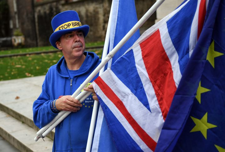 An anti-Brexit demonstrator holds a European Union flag and a British Union flag, also known as a Union Jack, in London Thurs
