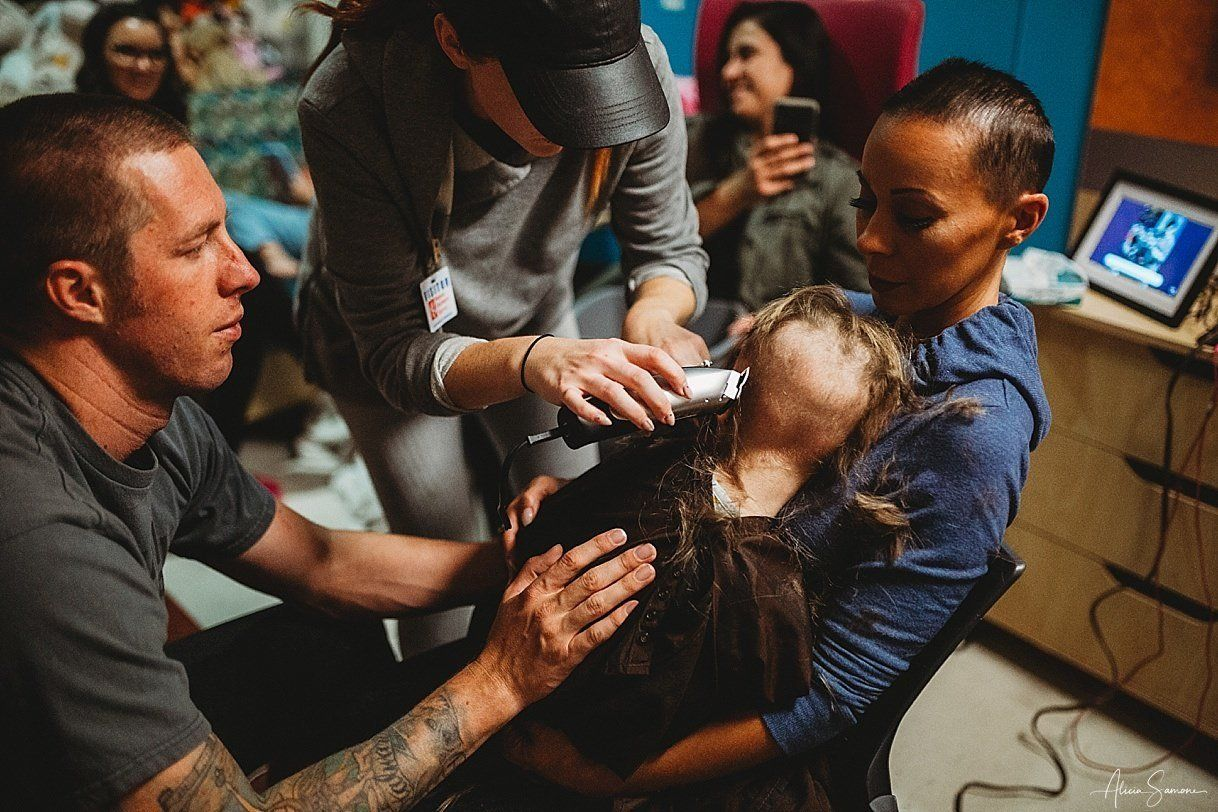 Madi, 5, is held by her mother, Ashley, and her father, Chris, as the three get their hair cut together.