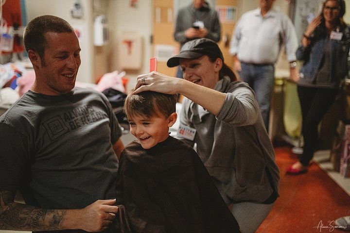 Madi's father, Chris, and her brother sit down for haircuts to show support after acute myeloid leukemia treatment caused her