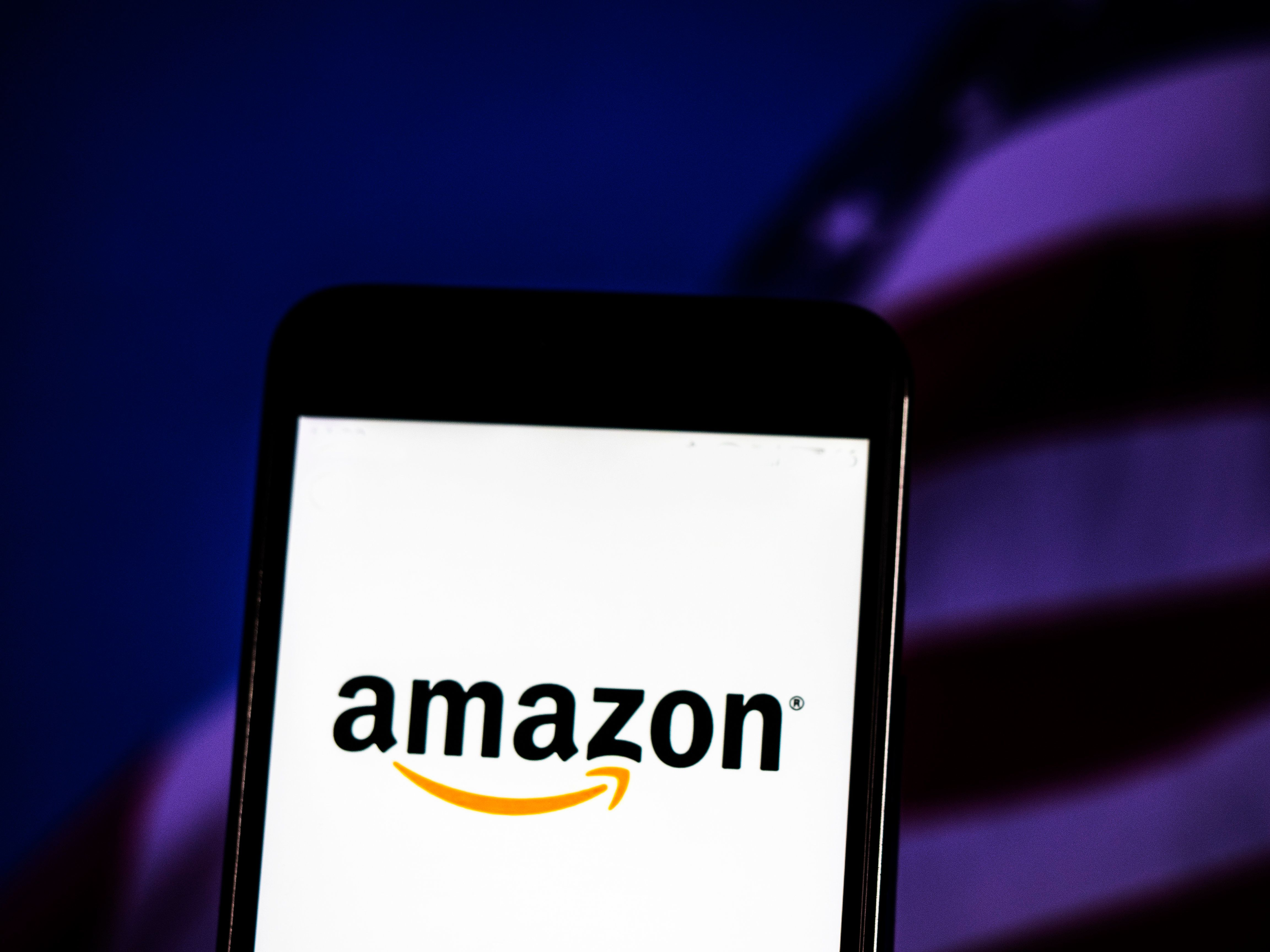 KIEV, UKRAINE - 2018/11/06: The Amazon logo seen displayed on a smart phone with a background of a stock market shedle. Amazon.com, Inc., doing business as Amazon, is an American electronic commerce and cloud computing company based in Seattle, Washington. (Photo by Igor Golovniov/SOPA Images/LightRocket via Getty Images)