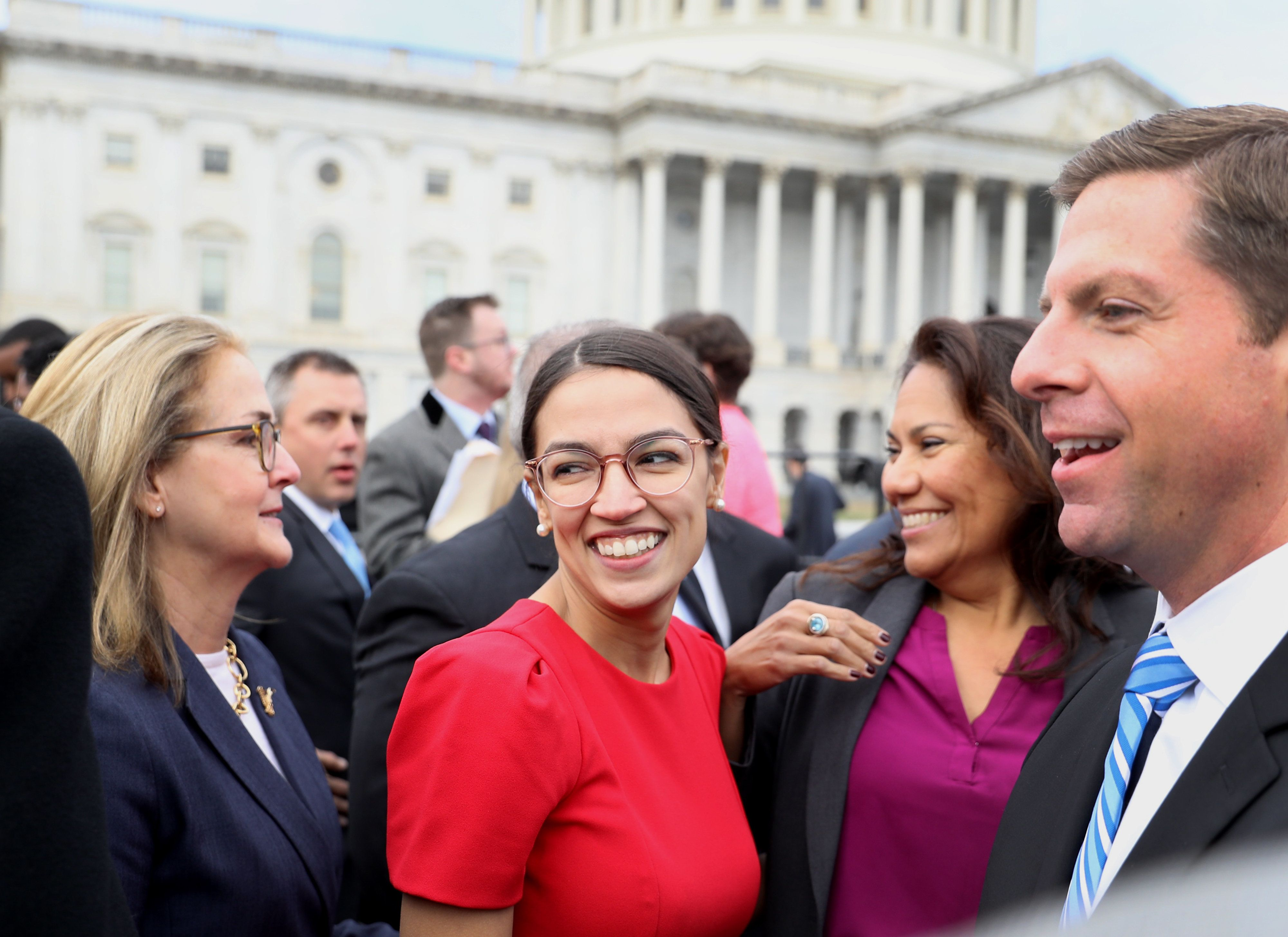 Representative-elect Alexandria Ocasio-Cortez, a Democrat from New York, smiles after a group photo with the 116th Congress outside the U.S Capitol in Washington, D.C., U.S., on Wednesday, Nov. 14, 2018. Congress returns to work this week with Democrats and Republicans promising to work together to avert a partial government shutdown and pass a handful of other bills, though President Donald Trump's demand to fund his border wall could blow up their plans. Photographer: Andrew Harrer/Bloomberg via Getty Images