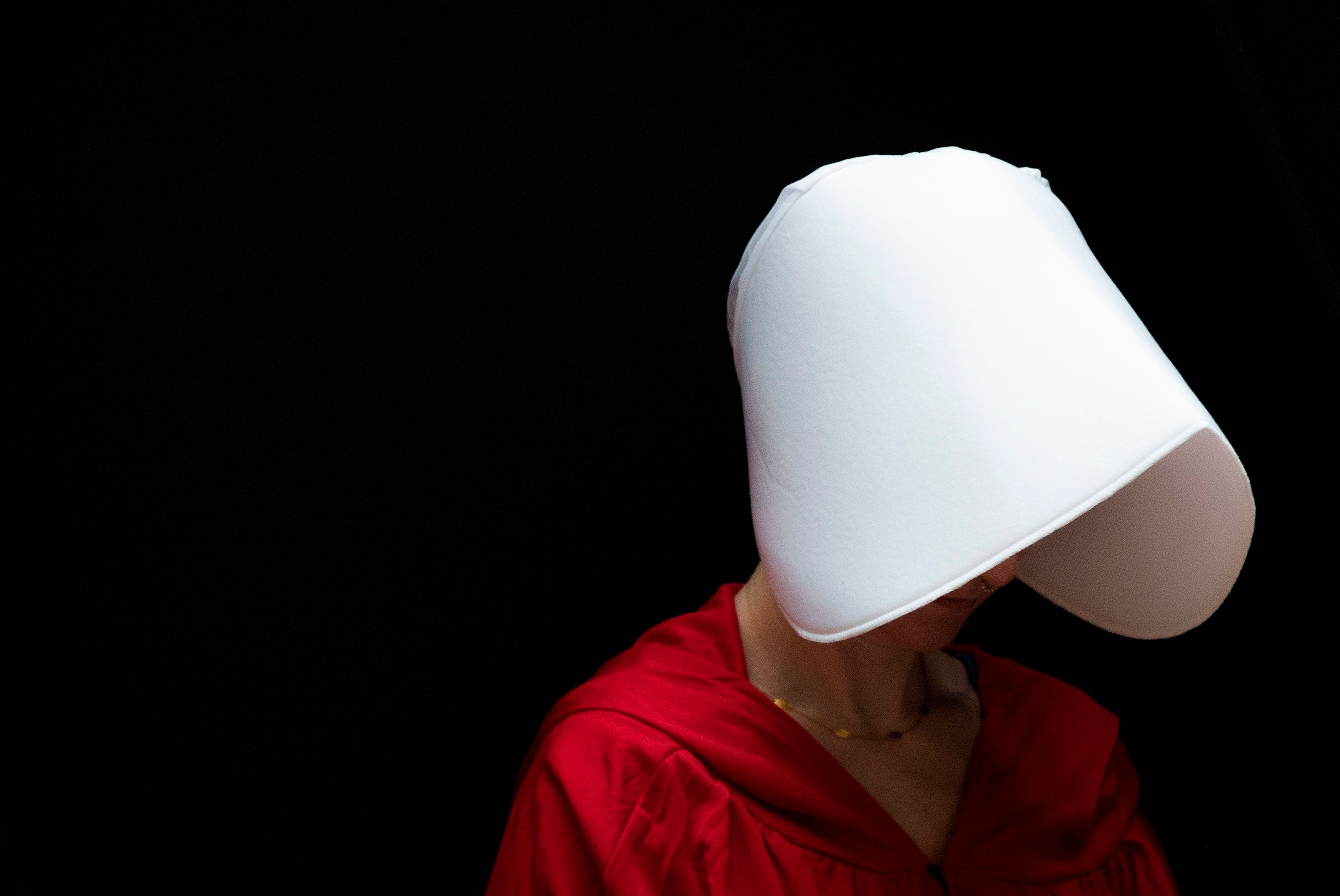 TOPSHOT - A woman dressed as a character from the novel-turned-TV series 'The Handmaid's Tale' walks through the Hart Senate Office Building as Supreme Court nominee Brett Kavanaugh starts the first day of his confirmation hearing in front of the US Senate on Capitol Hill in Washington DC, on September 4, 2018. - President Donald Trump's newest Supreme Court nominee Brett Kavanaugh is expected to face punishing questioning from Democrats this week over his endorsement of presidential immunity and his opposition to abortion. Some two dozen witnesses are lined up to argue for and against confirming Kavanaugh, who could swing the nine-member high court decidedly in conservatives' favor for years to come. Democrats have mobilized heavily to prevent his approval. (Photo by Jim WATSON / AFP)        (Photo credit should read JIM WATSON/AFP/Getty Images)