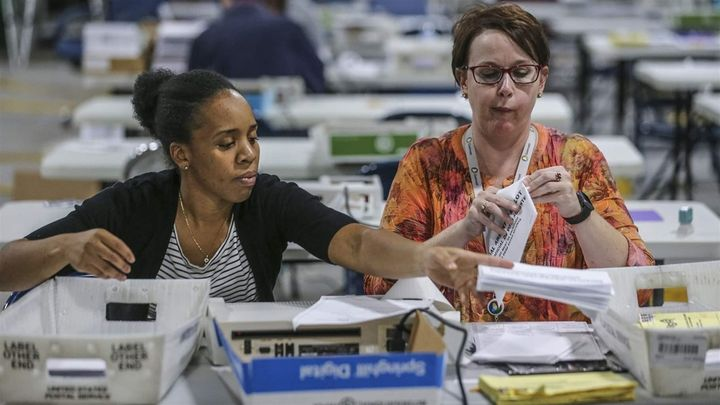 Election officials in Gwinnett County, Georgia, open and scan absentee ballots during the midterm election count. Untradition
