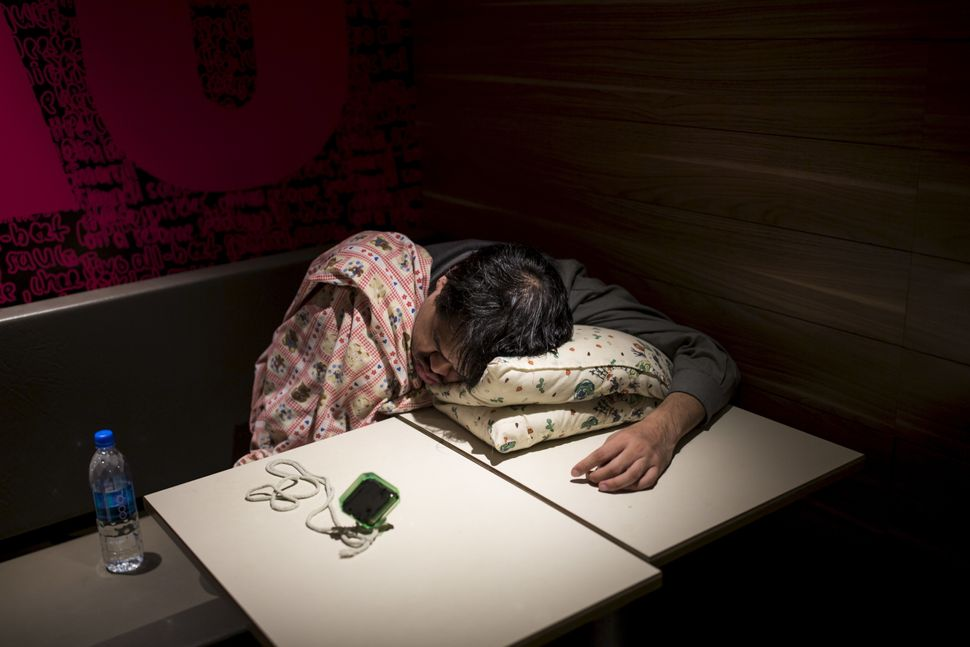 One of Hong Kong's McRefugees sleeps at a 24-hour McDonald's with an alarm clock nearby to wake him up.