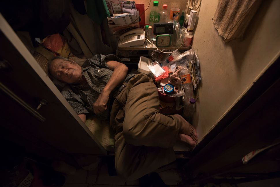 "Cheung Chi-fong, 80, sleeps in his tiny ""coffin cubicle,"" where he cannot stretch out his legs."