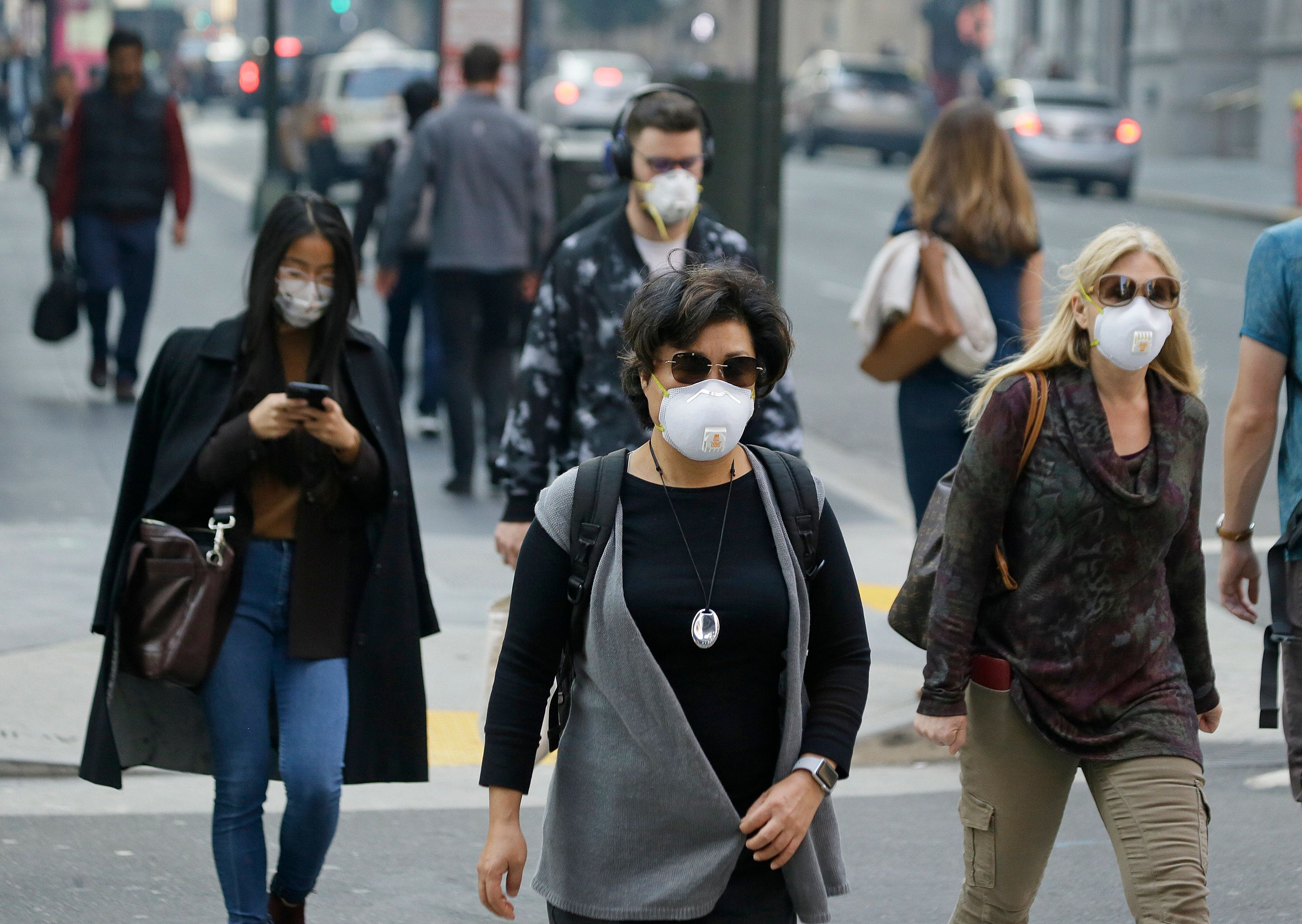 People wear masks while walking through the Financial District in the smoke-filled air Friday, Nov. 9, 2018, in San Francisco. Authorities have issued an unhealthy air quality alert for parts of the San Francisco Bay Area as smoke from a massive wildfire drifts south, polluting the air. Officials say the thousands of structures in the town of Paradise, 180 miles (290 kilometers) northeast of San Francisco, were destroyed by the blaze that has charred 110 square miles (285 square kilometers). (AP Photo/Eric Risberg)
