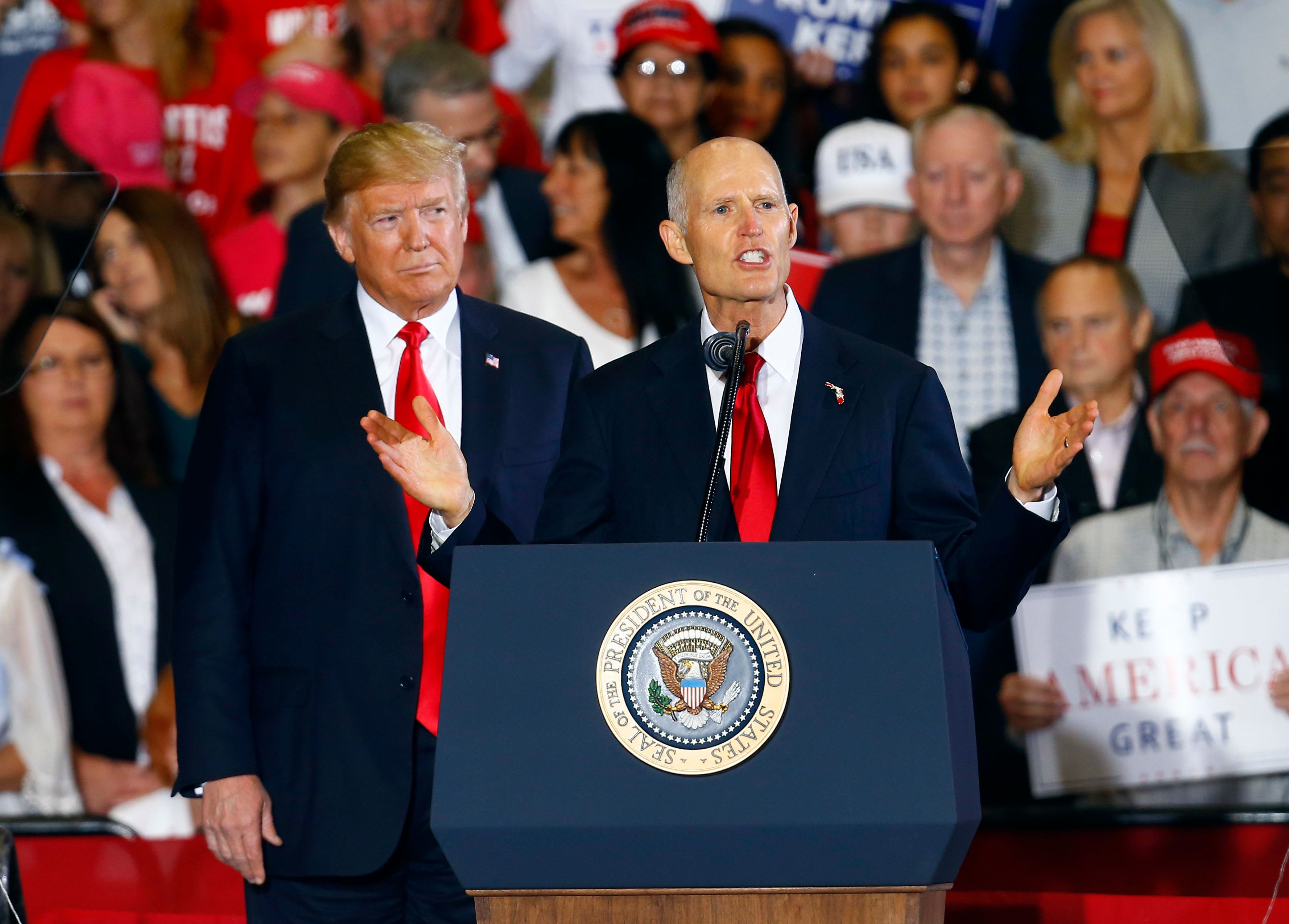 FILE- In this Nov. 3, 2018 file photo President Donald Trump stands behind Florida Governor Rick Scott as he speaks at a rally in Pensacola, Fla. Scott is challenging U.S. Senator Bill Nelson. Florida voters on Tuesday will elect a U.S. senator, a new governor, three Cabinet members and several new members of Congress while deciding to support or approve 12 proposed changes to the state's constitution. (AP Photo/Butch Dill, File)